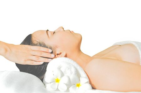 portrait of a young woman with eyes closed receiving facial massage photo