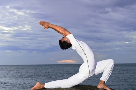young Asian man doing yoga on the beach Stock Photo - 14264700