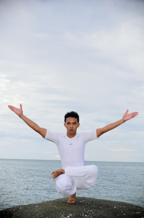 young Asian man doing yoga on the beach photo