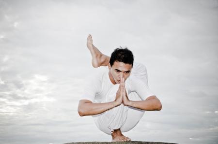 jungen asiatischen Mann macht Yoga am Strand