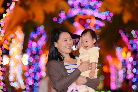 Mother and her baby enjoy colorful night light  Stock Photo - 14646942