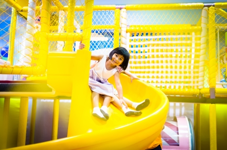 Happy little girl is playing on slider Stock Photo - 15719822