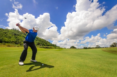 golfcourse: Golfer swinging his gear and hit the golf ball from tee to the fairway, slow shutter motion blur Stock Photo