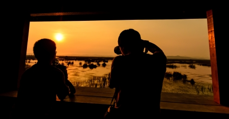Two photographer taking sunset photo with wooden window frame Stock Photo - 17971345