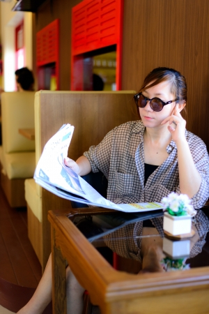 Asian woman reading newspaper in coffee shop photo