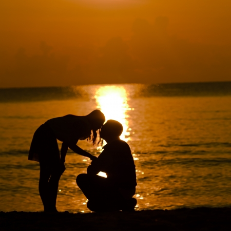 Woman kiss man and accept for proposal on the beach with sun rise Stock Photo - 19332791