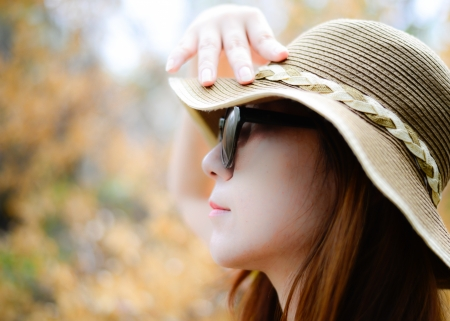 beautiful Asian woman wearing sunglasses and hat in the park on a warm autumn day