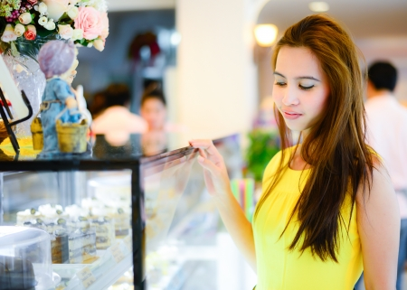 young Asian woman in front of sweet candy food store window photo