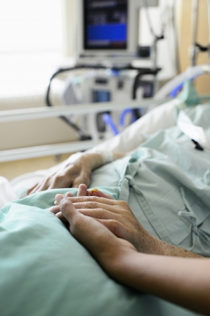 A young hand touches and holds an old wrinkled hand in hospital Stock Photo