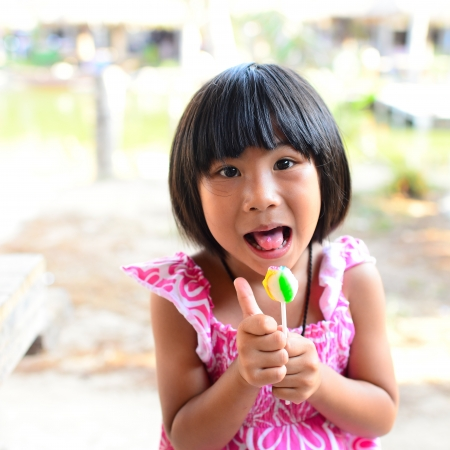cute little girl eating a lollipop in summertime photo