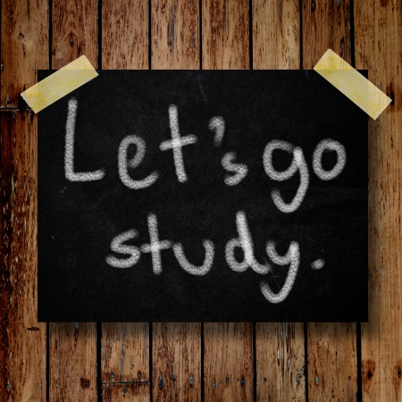 Let's go study on message note with wooden background