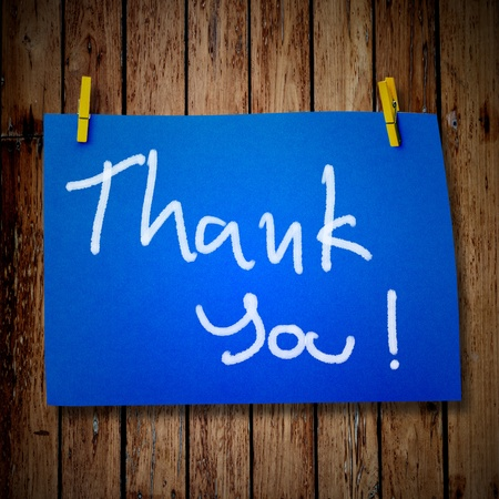 note paper and clothes peg on a wooden background with Thank you