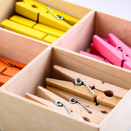 Coloured wooden cloth pins set in the box photo