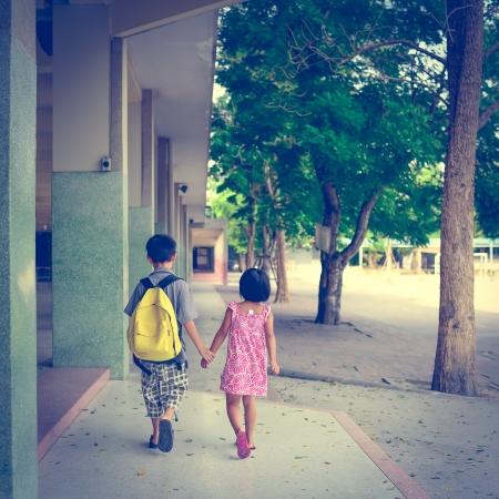 niños caminando: niño y niña caminando en la escuela con la celebración de sus manos