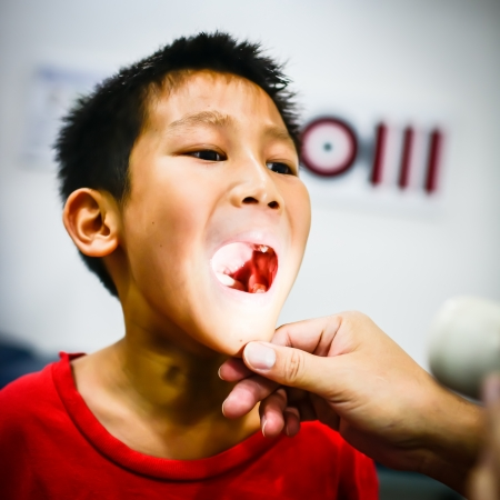 Boy showing his throat to doctor Stock Photo - 20883386