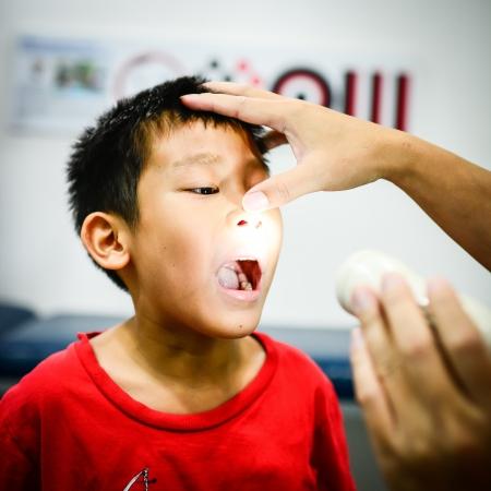의사에게 자신의 목을 보여주는 소년