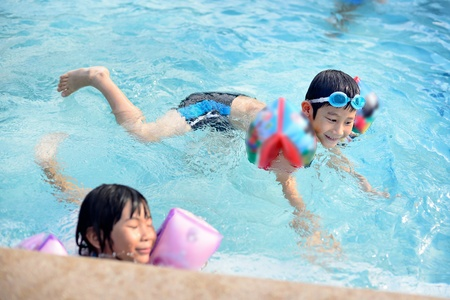 Gar�on asiatique en profitant de la piscine photo