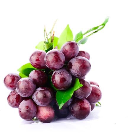 Verse rode druiven op een witte achtergrond.