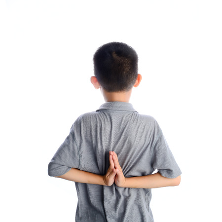 young boy doing yoga exercise in Virasana or Hero Pose with reversed prayer or namaste in studio against a mottled background from behind. photo