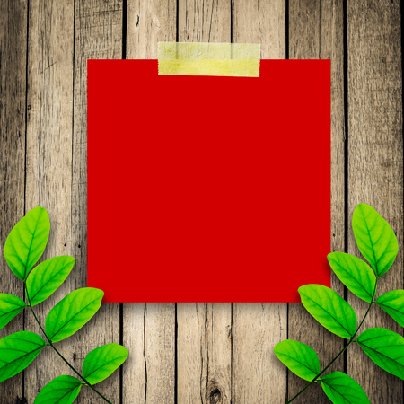 Red paper note and green leaves on the old wooden background  photo