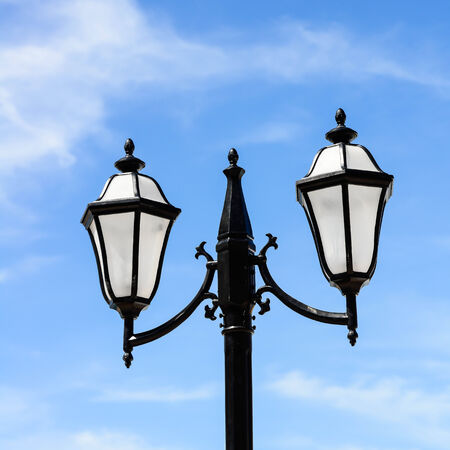 vintage iron lighting pole with twin double lamp lantern on background of dark blue sky.