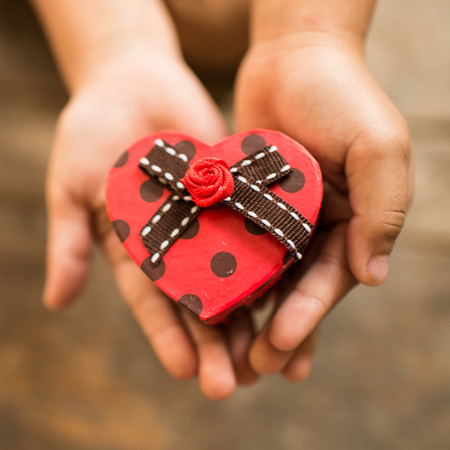 Red heart box in child's hands photo
