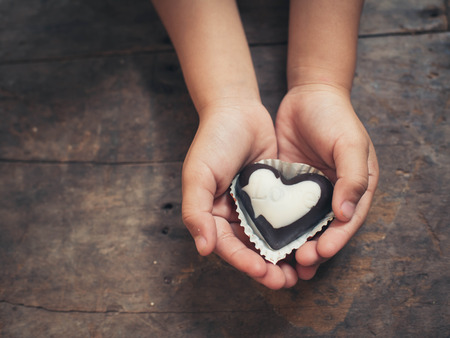Love note on black and white chocolate in kid's hand photo