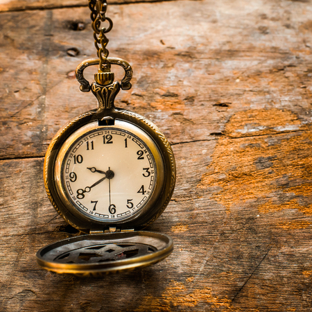 Vintage pocket watch on chain on wooden background with still life. photo