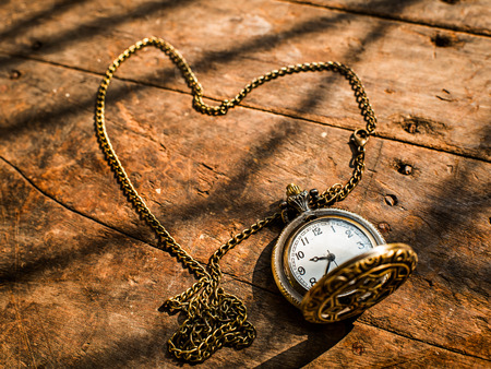 heart pocket watch on a wood background with natural light. photo
