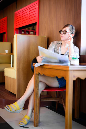 Asian woman reading newspaper in coffee shop. photo