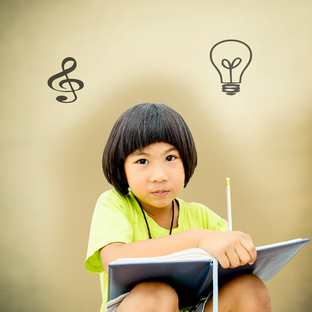 Cute little girl writing her homework on brown background photo