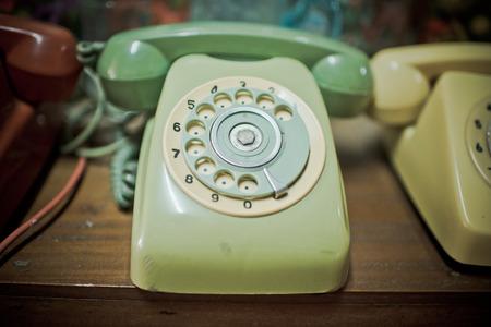 Retro greenTelephone on wooden table photo