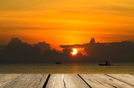 Wooden floor facing to Fishing boat when sun rising  photo