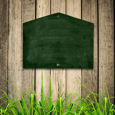 Blackboard with green grass on wooden background   photo