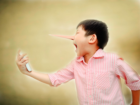 Long nose Angry Asian child shouting At Mobile Phone,liar concept Standard-Bild