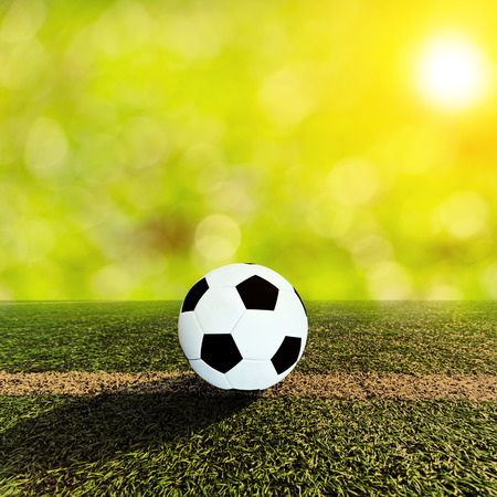 Ball on soccer field and orange sky and sun flare photo