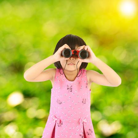 Girl with binoculars sun flare and green bokeh background photo