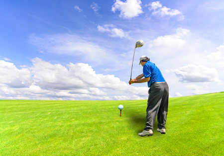 off course: Golfer swinging his gear and hit the golf ball from tee to the fairway, slow shutter motion blur Stock Photo