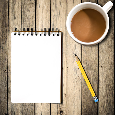 Notebook with pencil, coffee on wooden background photo