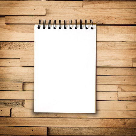 single face notebook on wood background with clipping path photo