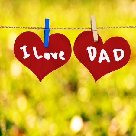 I love Dad message on Red heart shape on note paper attach to rope with clothes pins on yellow bokeh background photo