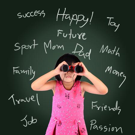 Portrait of a schoolgirl standing over blackboard and looking through binoculars with her mind map photo