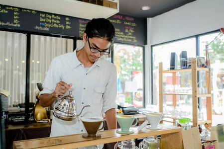 Young waiter making cup of coffee at coffee shop photo