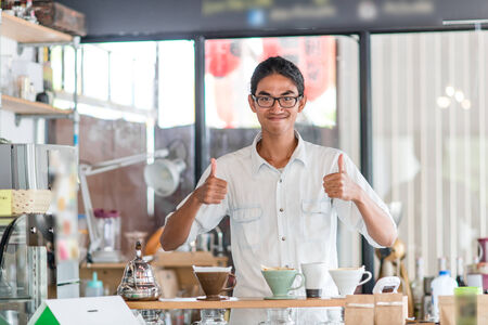 raising cans: Cheerful barista in coffee shop. Stock Photo