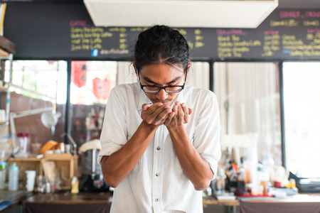 Barista smelling coffee beans in his hand. photo