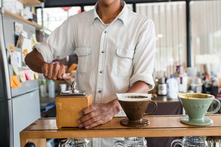 Barista make coffee grinder focus at hand. photo