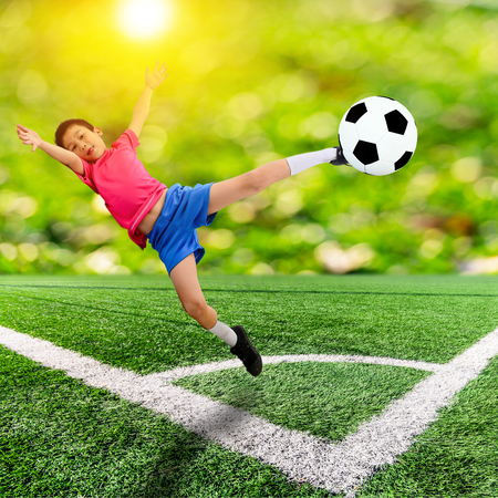 Asian boy with soccer ball on soccer field and orange bokeh and sun flare photo