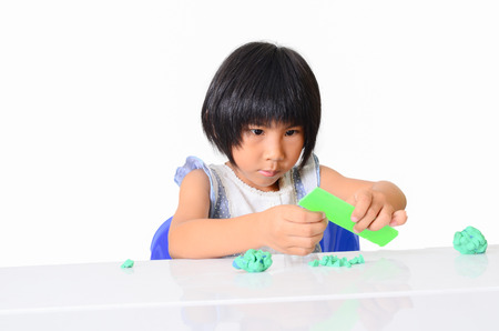 Little Asian girl is learning to use play dough in a well lit room isolated on white. photo
