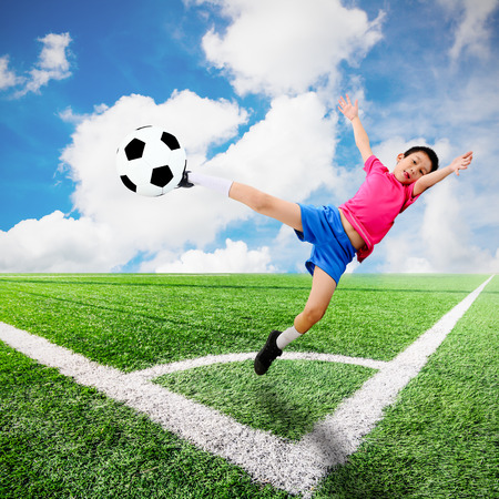 Asian boy with soccer ball at soccer field and blue sky photo