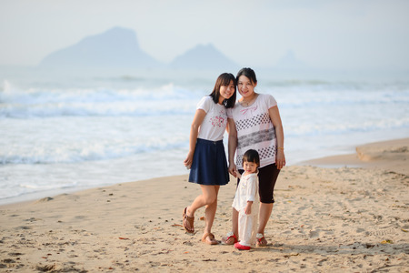 Happy Asian family, mother, sister and child on the beach. photo